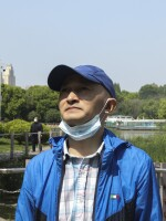 """Zhang Hai stands on a bridge where he took his father out for a walk only about four months earlier. His father died of the novel coronavirus on Feb. 1. """"The scenery is still here, but the person is gone,"""" he sighs. He says he frequently comes to this park """"looking for memories."""""""