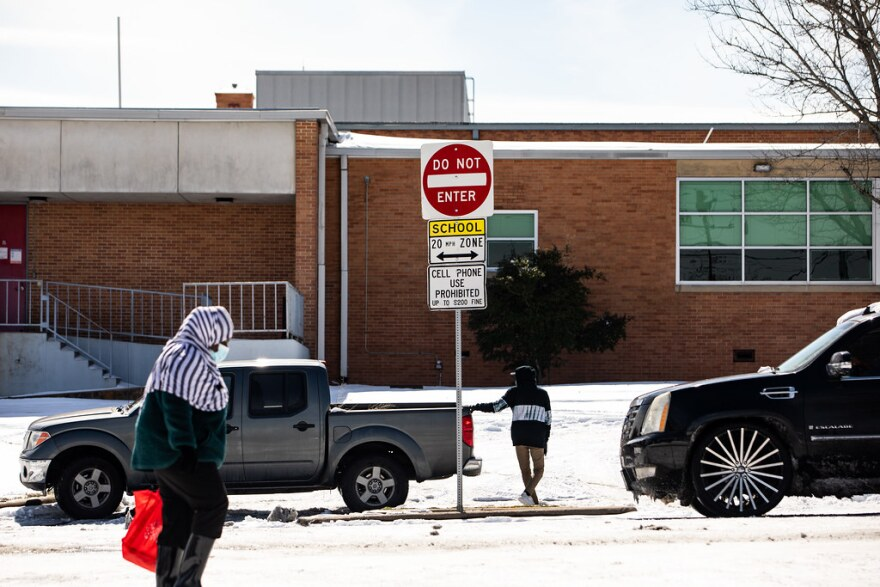 Un vehículo, atascado en la nieve frente a la escuela secundaria Travis en el sur de Austin.