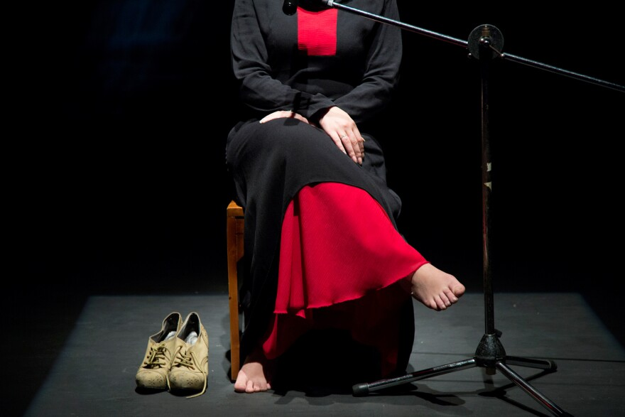 During the last rehearsal before opening night, a Syrian Palestinian refugee recounts onstage the day she went back to her house in the Yarmouk camp in Syria after it was bombed. The shoes beside her are the ones she was wearing that day she entered the camp.