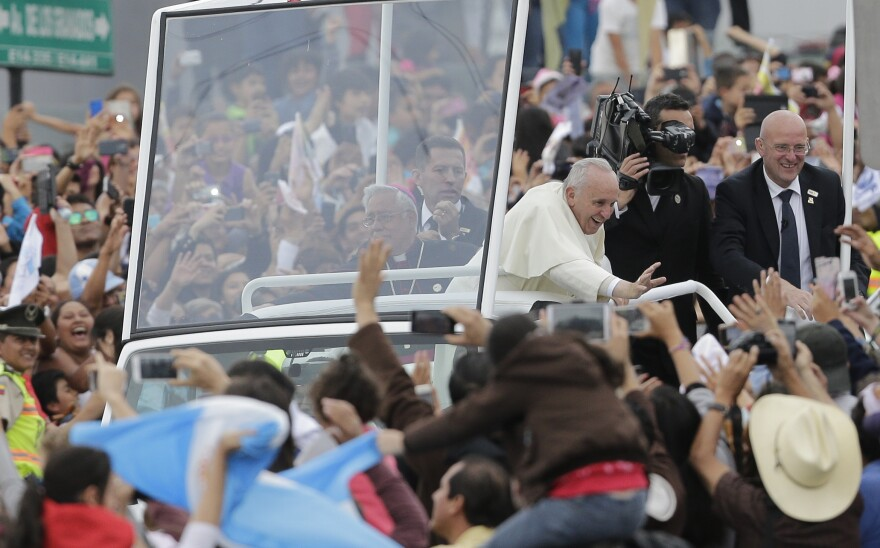 Pope Francis waves to the crowd as he rides aboard the Popemobile in the streets of Quito, Ecuador, on Sunday.