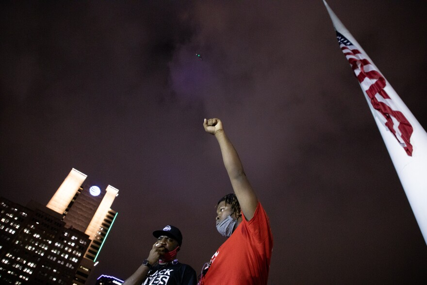 Photo of demonstrator outside Dallas City Hall with a raised fist. The light of a helicopter can be seen in the sky above.