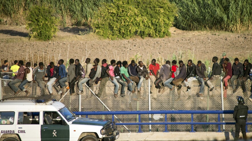 African migrants climb a border fence between Morocco and Spain's North African enclave of Melilla on Tuesday as Spanish civil guard officers stand under them.