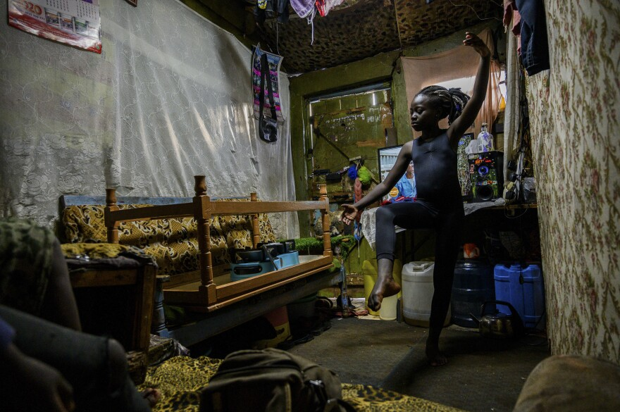 Valentine Ayuma, a 10-year-old ballet dancer, follows a Facebook Live stream at home. The dance session was organized by Mike Wamaya, founder of the nonprofit Project Elimu. Due to lockdowns when the pandemic began, students in Kenya were trained via streamed recordings. <em>May 22. Kibera, Kenya.</em>