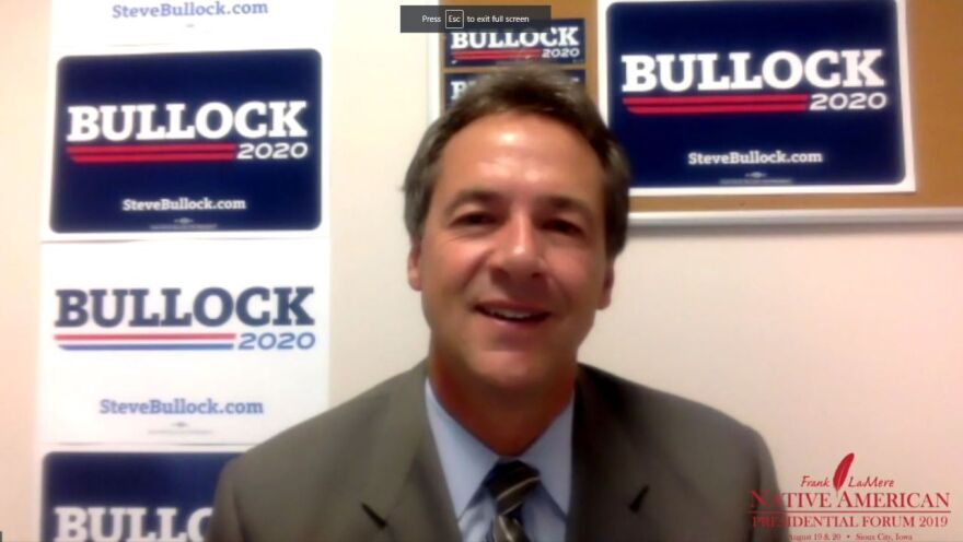 Montana Governor Steve Bullock sits in front of campaign signs.