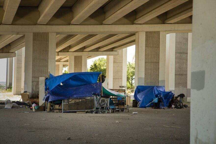 A homeless encampment under a bridge