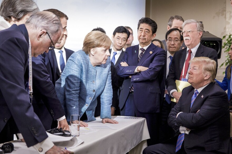 German Chancellor Angela Merkel, center, speaks with President Trump while surrounded by other world leaders during the G7 Leaders Summit in La Malbaie, Quebec, Canada in June.