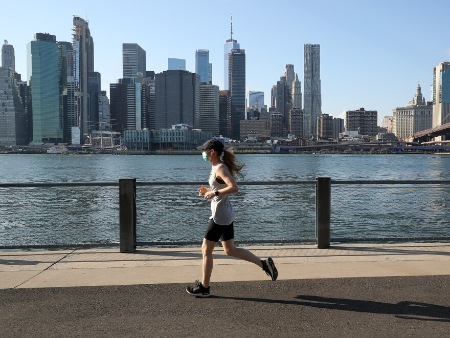 A woman runs with her face mask on Monday in New York City, where the mayor has announced that city personnel will hand out free masks to anyone who is not wearing a face covering.