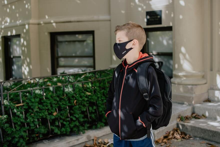 A boy wearing a backpack and a facemask stands near the front steps of a school.