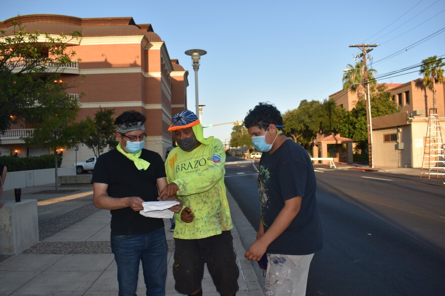 Antonio Briones (center) works with artists and volunteers on the street mural in Laredo.