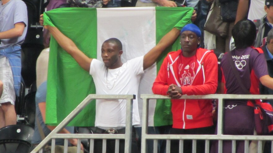 Nigerian fan Ifeoluwa Akande holds his country's flag as he watches Nigeria's basketball team lose to the United States by a record 83 points.
