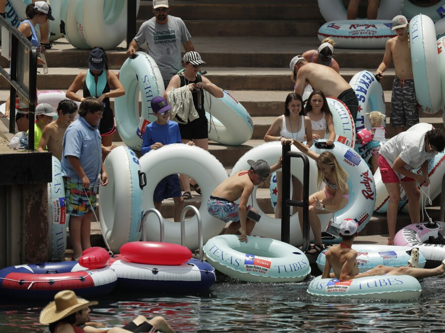 "Tubers prepare to float the Comal River in New Braunfels, Texas, on Thursday. Texas Gov. Greg Abbott said Wednesday that the state is facing a ""massive outbreak"" of the coronavirus and that some new local restrictions may be needed to preserve hospital space for new patients."