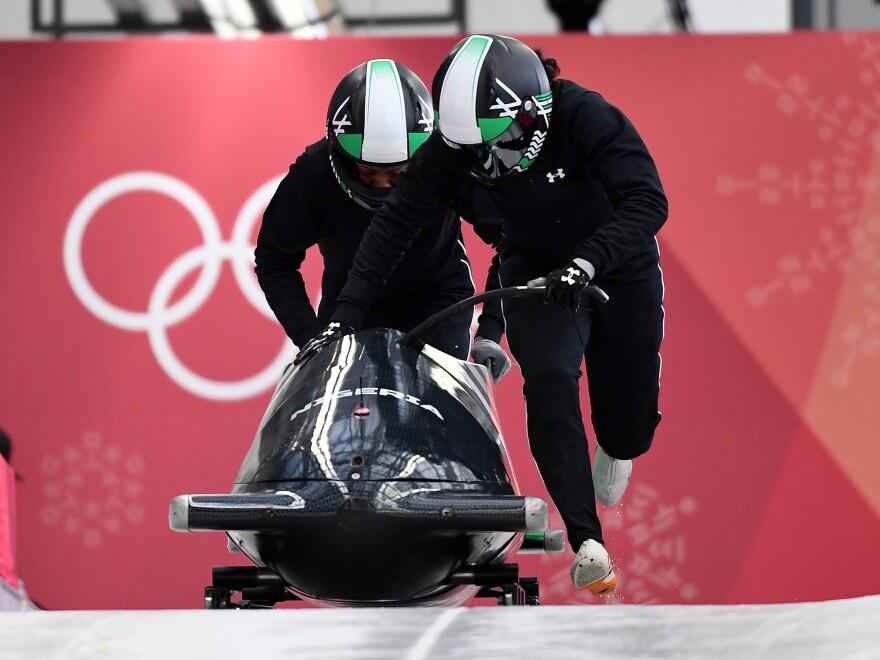 Team captain Seun Adigun of Nigeria (right) starts a run at the Olympic Sliding Centre.