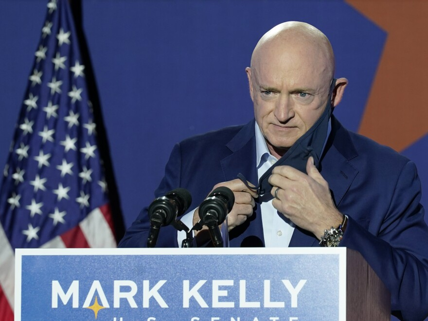 Senate-Elect Mark Kelly, removes his mask as he prepares to speak at an election night event in Tucson, Ariz.