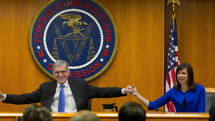 Federal Communication Commission Chairman Tom Wheeler joins hands with Commissioner Jessica Rosenworcel ahead of a February 2015 hearing in Washington, D.C.