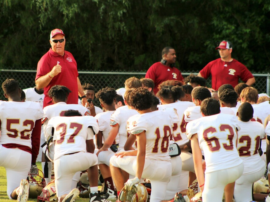Russell County High School football coach Mark Rose speaks to players during a spring game in 2019. He's against having his team play this season without state-mandated coronavirus testing. Alabama high school officials, like in many other states, say there's not enough money for tests.