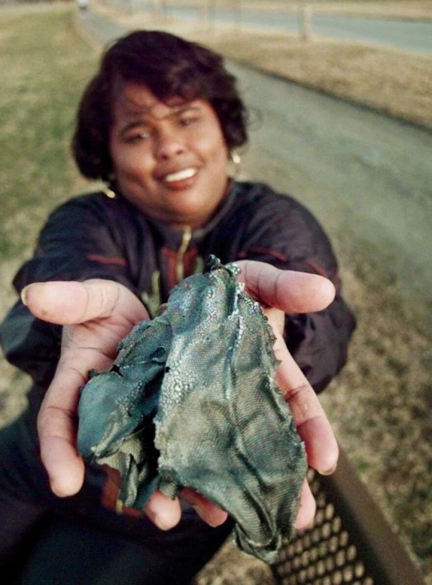Lottie Williams holds a piece of a Delta II rocket that fell from the sky and hit her in the back while she was walking on a trail in Tulsa, Okla., in 1997.