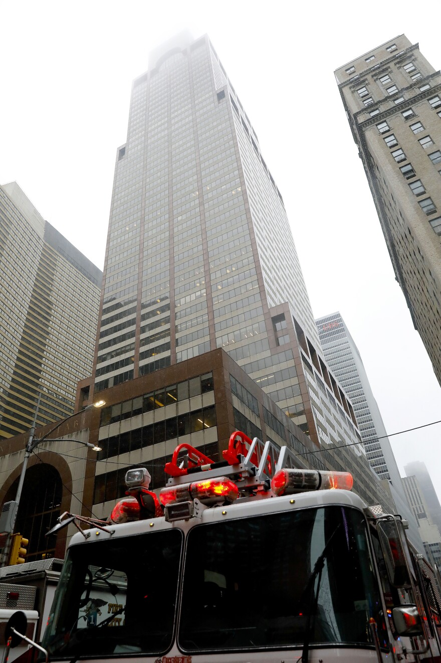 New York firefighters respond to the scene where a helicopter was reported to have crash landed on top of a building in Manhattan on Monday.