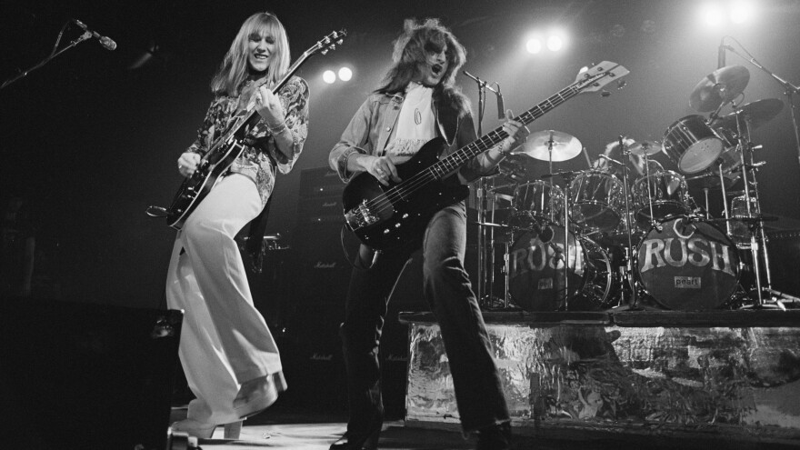 Alex Lifeson (left) and Geddy Lee (with Neil Peart on drums) on stage in 1976 on the tour that followed the release of <em>2112</em>.