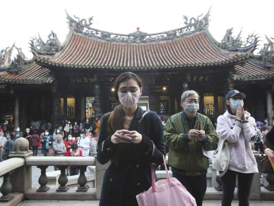 People wear face masks to protect against the spread of the coronavirus as they pray at the Longshan Temple in Taipei, Taiwan, on Thursday. Taiwan has reported a relatively low number of cases of the virus despite its proximity to China, where the virus was first detected.