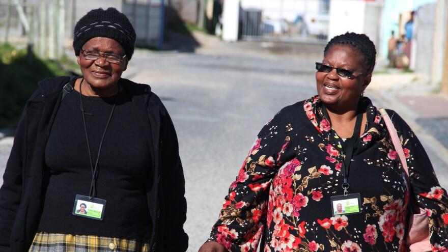 Thami Mlotaywa (left) and Gloria Gxebeka go door to door, checking on the health of aging neighbors.
