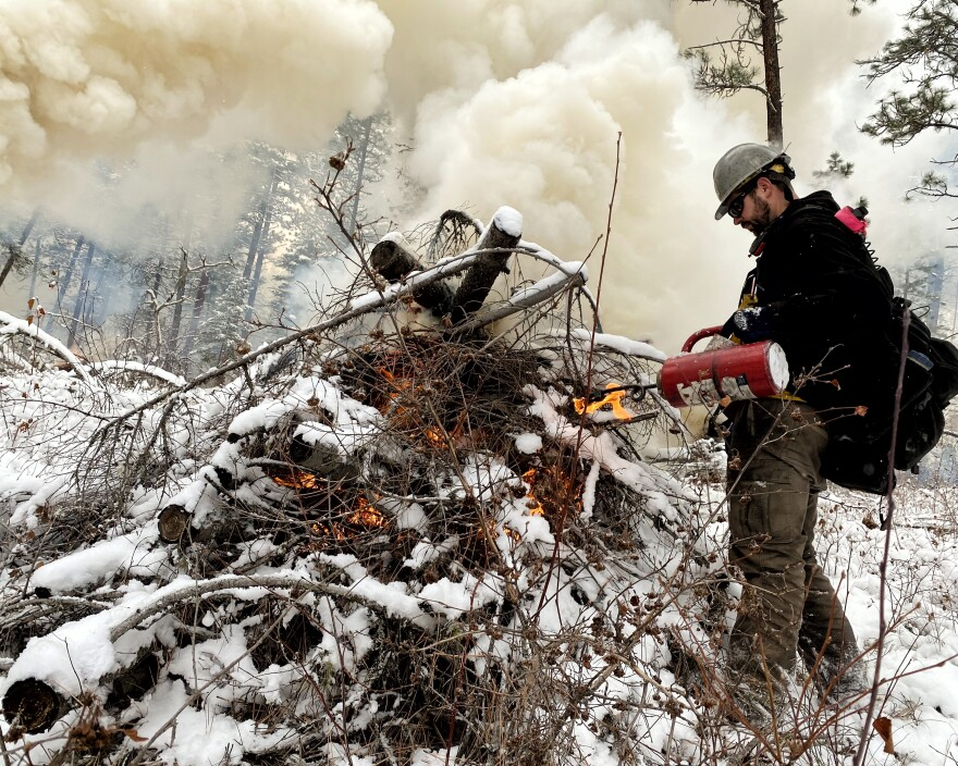 Stryker Clark tips a red, lit drip torch over a snow covered pile of logs and twigs.