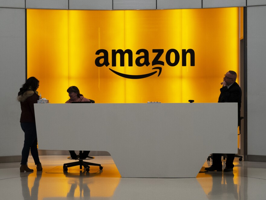 People stand in the lobby of Amazon offices in New York in January 2019. At a time of mass work from home and many moving to spacious suburbs, Amazon is funding a large expansion of corporate real estate and jobs in New York and five other U.S. cities.