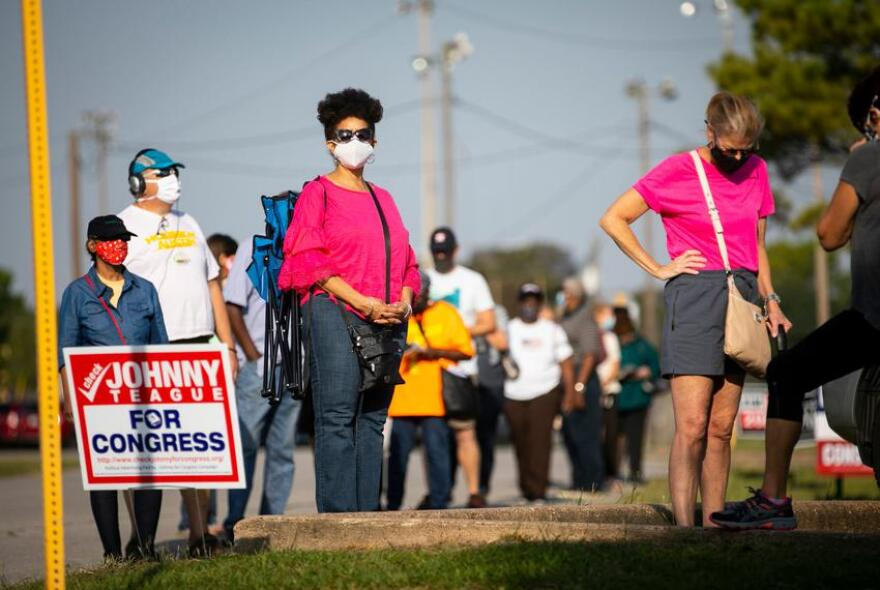 Harris County residents wait in line at Houston's Bayland Community Center during the first day of early voting.
