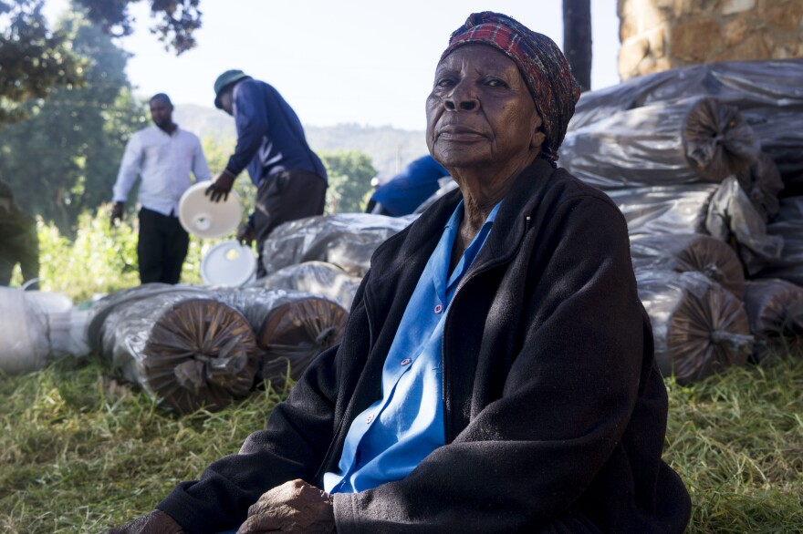Annie Machokote waits for the distribution of buckets and soap to be distributed for washing up. She is also waiting for a new supply of her blood pressure medicine.