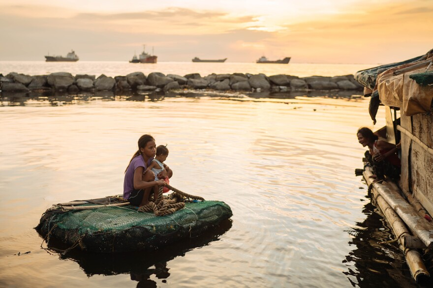 Joan Garcia became pregnant at 14 and gave birth at 15. She and her child travel by raft between the two shacks where they live in Navotas fish port on Manila Bay.