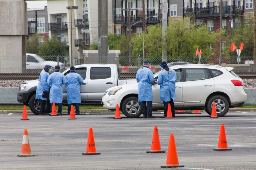 Staff work at a drive-through coronavirus testing site outside the American Airlines center in North Dallas in late March.