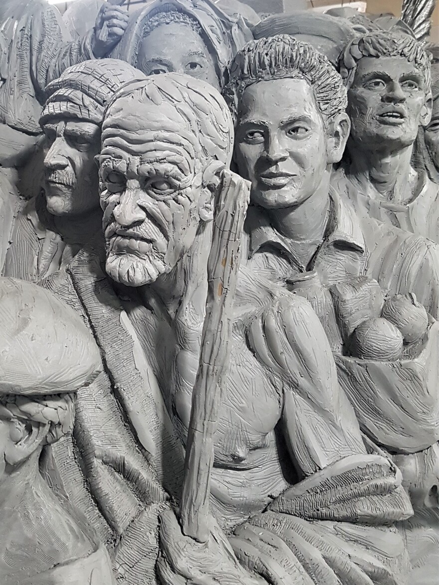 "The Italian emigrant behind the man holding the staff carries the bag of bread and fruit — ""a metaphor for nourishment,"" says the sculptor, Timothy Schmalz. In this photo, the sculpture is still in the clay stage, before the bronzing."