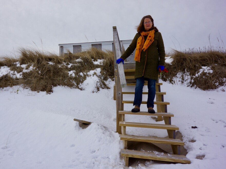 Laura Wing in front of her beachfront home in Sandwich. Wing has not installed fiber rolls. This natural dune helps protect her home from erosion for now, but spring storms could make it vulnerable.