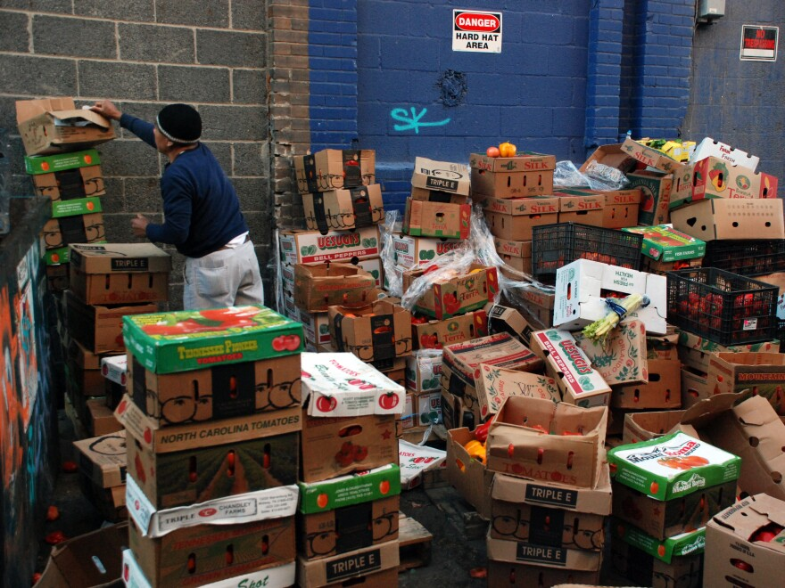 Boxes of unsold produce sit stacked outside Mexican Fruits, a discount grocer. A few loads will be donated to churches but the rest will be thrown away.