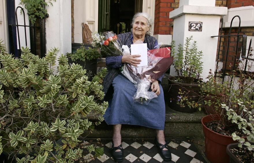 British writer Doris Lessing holds flowers and tributes as she sits outside her north London home in October 2007 after winning the Nobel Prize.