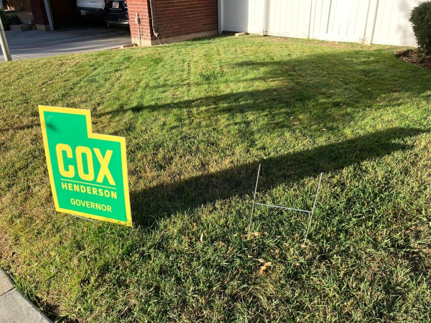 A political yard sign sits next to an empty stand.