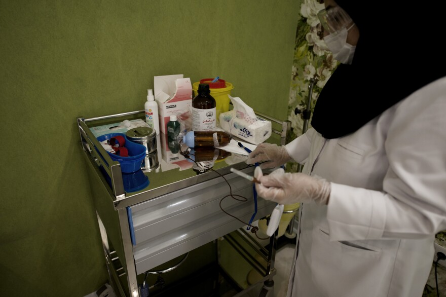 A nurse prepares chemotherapy medications for patients at the Roshana Cancer Center. An oncologist there says the limitation goes beyond goods and supplies.