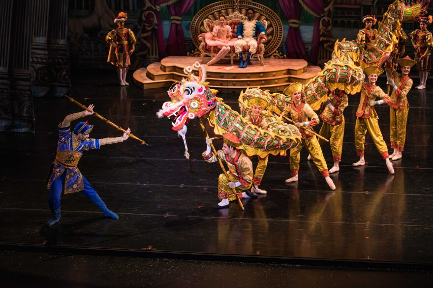 Photo of dancers on stage in brightly colored costumes.