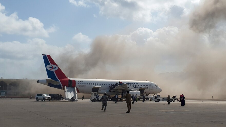 Smoke billows behind a plane that brought Yemen's new government to Aden International Airport Wednesday. Explosions rocked the Yemeni airport shortly after the plane arrived.
