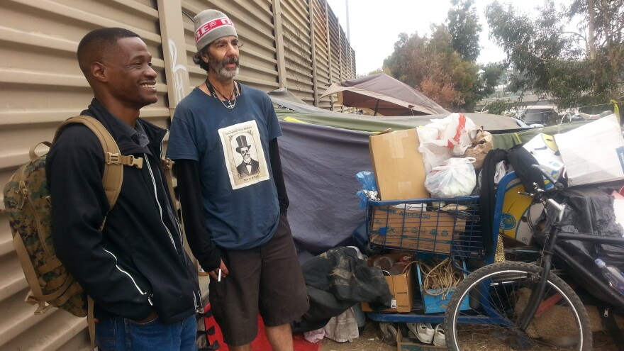 Jesse Henderson (left), an Army veteran, walks Hollywood Boulevard in Los Angeles looking for homeless veterans. His job is to try and connect them with support resources, including transitional housing, offered by the nonprofit U.S.Vets.