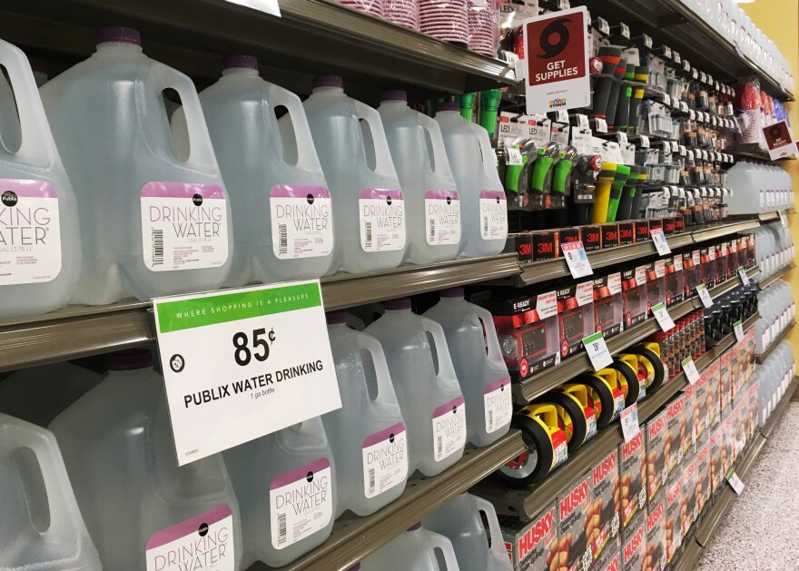Gallons of drinking water sits on shelves.