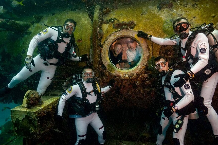 """Dominic D'Agostino (far left) and his fellow """"aquanauts"""" pose outside the Aquarius Reef Base habitat, where the researchers' support team join them."""