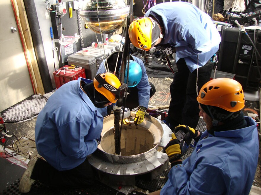 After the sensors are threaded onto the cable, the IceCube deployment team lowers them into the hole.