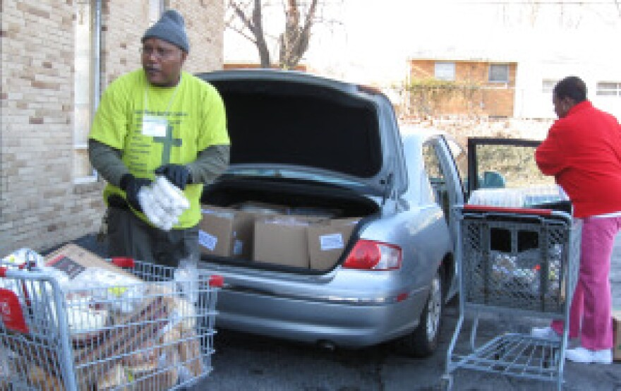 Dlarce Austin, right, a sister of Good News Baptist Church helps Austin Jones unload his car. Shopping carts are key to moving food at the pantry.