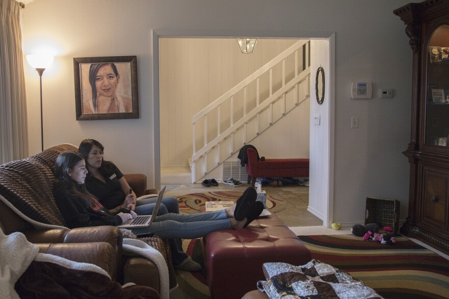 "Evelyn and April sit below a portrait of Carmen. The painting, acrylic on canvas, is by Parkland artist Nava Lundy, who created portraits of all 17 Parkland victims and gave them to the families. ""I just felt this urgency,"" Lundy says. ""I felt like I had to do something to help the families in whatever way I could."""
