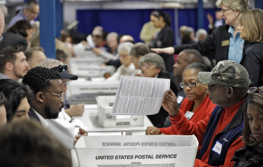 People sit at long tables picking up ballots and reading them.