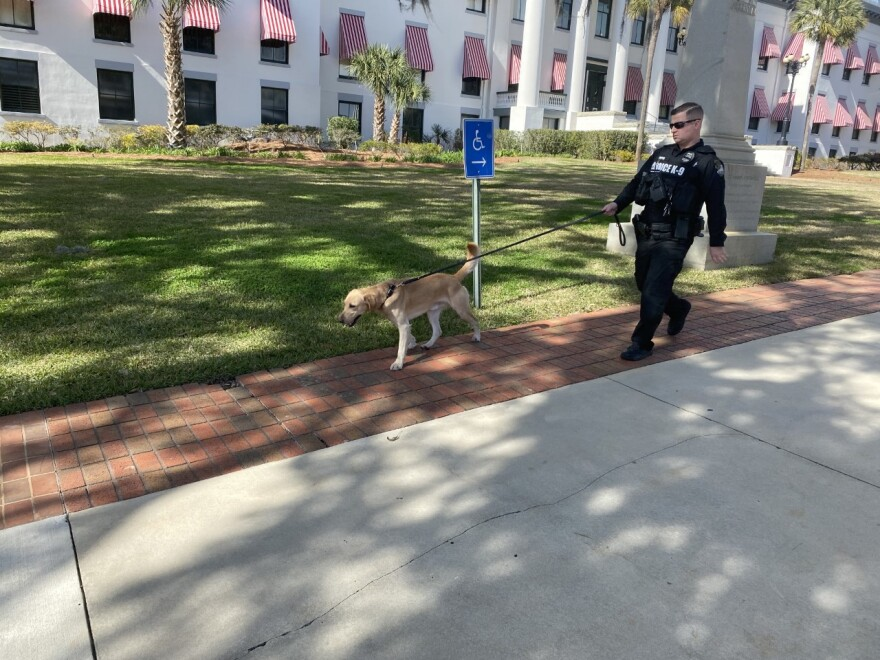 A Florida Department of Law Enforcement officer walks the capitol complex with a bomb-sniffing dog