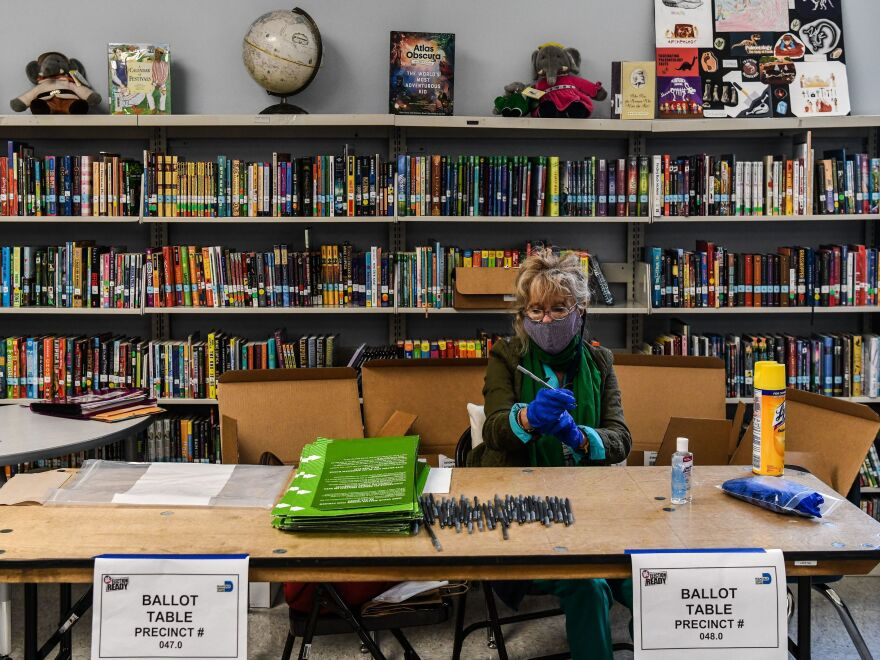 An election worker wears protective gloves during the Florida primary election at South Pointe Elementary School in Miami, on Tuesday.