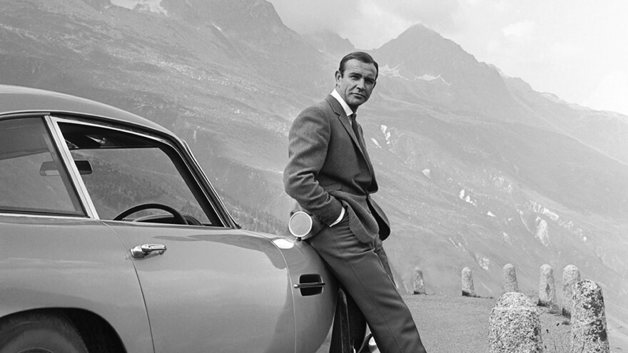 Actor Sean Connery poses as James Bond next to his Aston Martin DB5 in a scene from the United Artists release 'Goldfinger' in 1964.