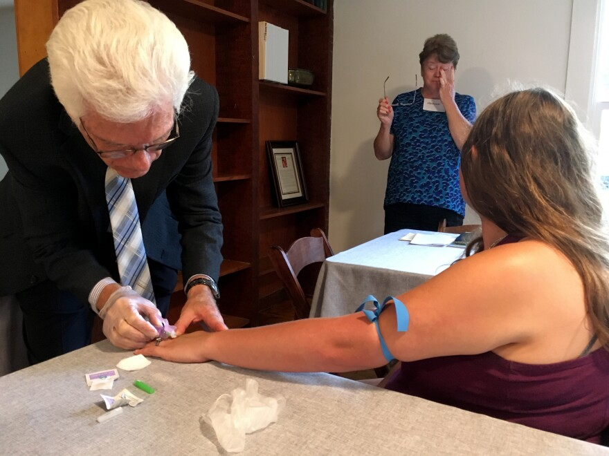 Steve Wickham, who is a nurse, draws blood at the midpoint of his and his wife Karen's six-week diabetes seminar. The hemoglobin A1c levels measured by the lab test help patients monitor whether the diet and exercise changes they're engaged in are making a difference in their blood sugar levels.