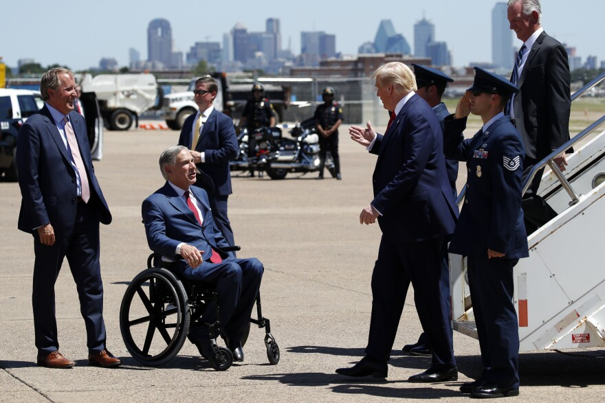 Ken Paxton and Greg Abbott greet Donald Trump at the bottom of the stairs of a plane at Dallas Love Field Airport.